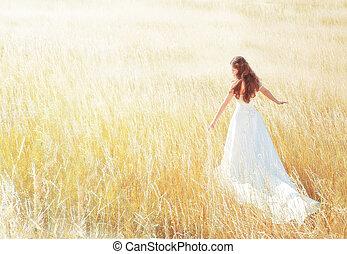 Mujer caminando en la pradera soleada el día de verano tocando hierba