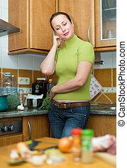 Mujer cansada en la cocina