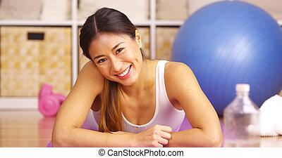 Mujer china feliz tumbada en el tapete de yoga