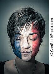 Mujer con bandera de Francia en la cara y ojos cerrados