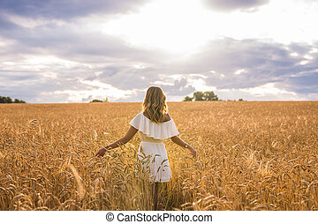 Mujer con brazos extendidos en un campo de trigo
