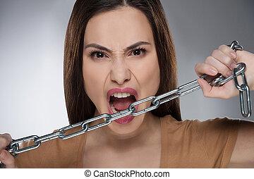 Mujer con cadena. Una joven agresiva sosteniendo una cadena y mirando la cámara mientras está aislada en gris
