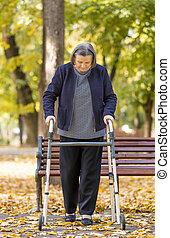 Mujer con caminante caminando al aire libre
