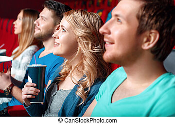 Mujer con coca en el cine entre espectadores