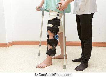 Mujer con rodillera en el entrenamiento asistida por fisioterapeuta