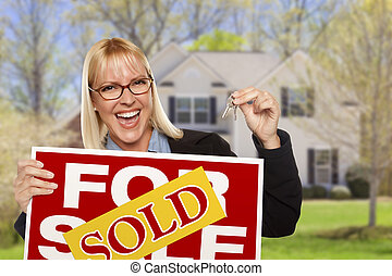 Mujer con señas vendidas y llaves en frente de casa