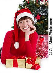 Mujer con sombrero rojo de Santa, tumbada bajo el árbol de Navidad con regalos