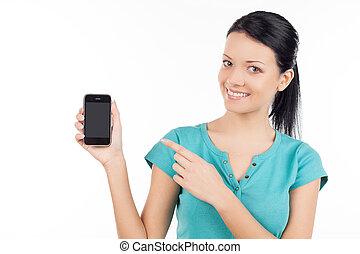 Mujer con teléfono móvil. Una joven alegre sosteniendo el móvil y apuntándolo mientras está aislada en blanco