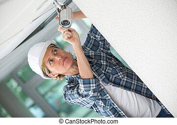 Mujer contratista instalando cámara de vigilancia