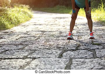 Mujer corredora cansada tomando un descanso después de correr duro en el sendero del bosque