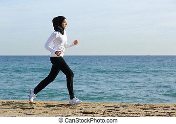 Mujer corredora de saudí árabe corriendo por la playa