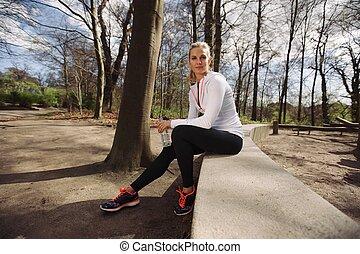 Mujer corredora descansando de entrenar en la naturaleza