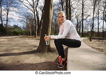 Mujer corredora tomando un descanso de correr en el bosque