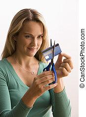 Mujer cortando la tarjeta de crédito
