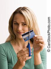 Mujer cortando tarjeta de crédito
