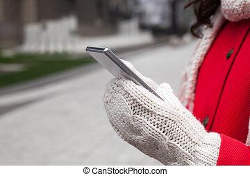 Mujer de abrigo rojo con smartphone en las manos pasando por la ciudad