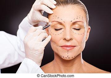 Mujer de mediana edad preparándose para cirugía plástica