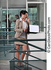 Mujer de negocios al teléfono, fuera de una oficina