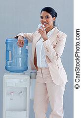 Mujer de negocios bebiendo de un refrigerador de agua