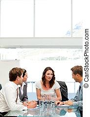 Mujer de negocios carismáticos hablando con su equipo