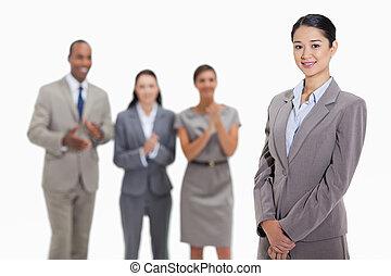 Mujer de negocios con compañeros de trabajo aplaudiendo en el fondo