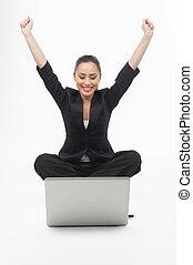 Mujer de negocios con portátil. Una joven mujer de negocios alegre mirando el monitor de la computadora y sosteniendo sus brazos levantados mientras se aislaba en blanco