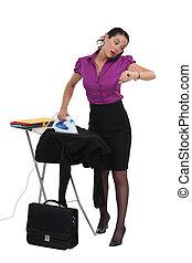Mujer de negocios con prisa planchando su traje