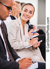 Mujer de negocios en la conferencia. Vista lateral de la gente de negocios sentada en una fila y escribiendo algo en sus libretas mientras una joven confiada mirando a la cámara y sonriendo