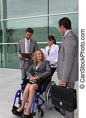 Mujer de negocios en silla de ruedas con colegas fuera de un edificio de oficinas