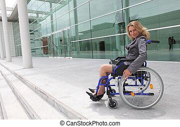 Mujer de negocios en silla de ruedas fuera de la oficina