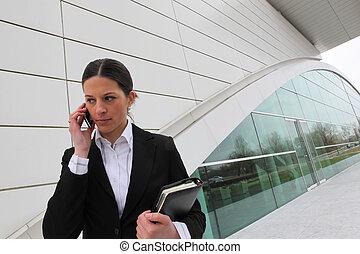 Mujer de negocios en un celular fuera de un edificio de oficinas