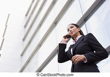 Mujer de negocios hablando por celular afuera