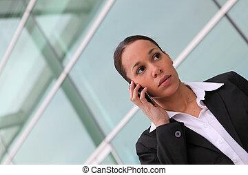 Mujer de negocios haciendo una llamada cerca de la oficina