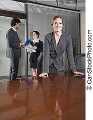 Mujer de negocios segura, colegas de fondo