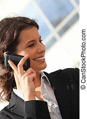 Mujer de negocios sonriente en el teléfono fuera de un edificio de oficinas