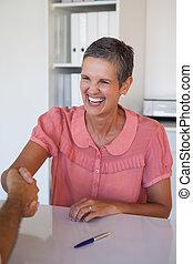 Mujer de negocios sonriente estrechando la mano en el escritorio
