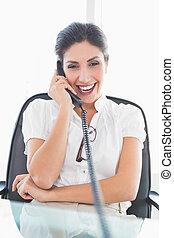 Mujer de negocios sonriente sentada en su escritorio al teléfono