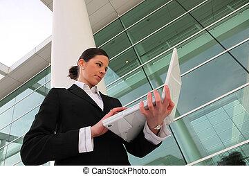 Mujer de negocios usando su portátil fuera de la oficina