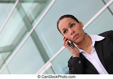 Mujer de negocios usando un celular fuera de una oficina