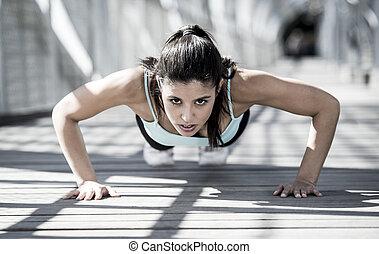 Mujer deportiva atlética haciendo flexiones antes de correr en entrenamiento urbano