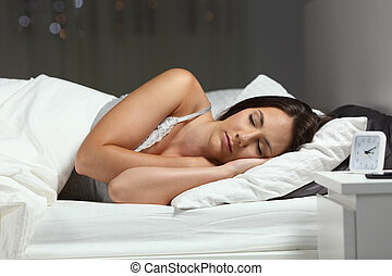 Mujer durmiendo profundamente en una cama en la noche