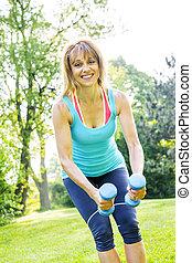 Mujer ejercitando con pesas en el parque