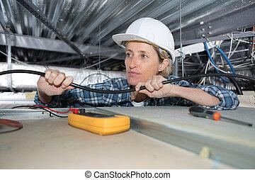 Mujer electricista instalando aparatos eléctricos en el techo