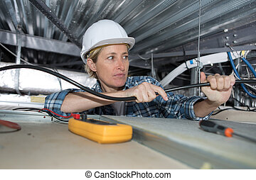 Mujer electricista instalando ventilación en el techo