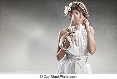 Mujer elegante sosteniendo un perro pequeño