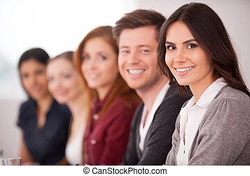 mujer, ella, sentado, cámara, gente, joven, seminar., mientras, otro, atractivo, atrás, sonriente, fila
