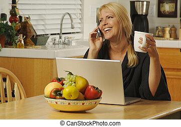 Mujer en la cocina en celular y portátil