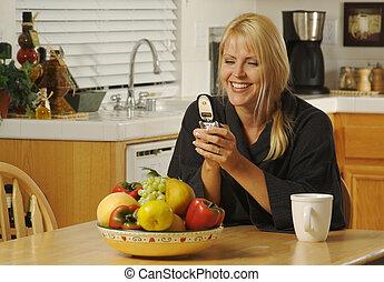 Mujer en la cocina usando teléfono celular