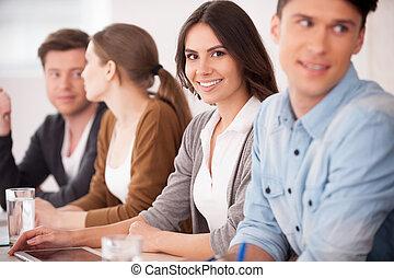 Mujer en seminario. Un grupo de jóvenes sentados juntos en la mesa mientras una mujer hermosa mirando a la cámara y sonriendo