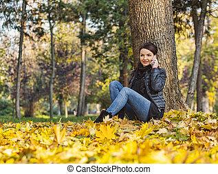Mujer en un móvil en un bosque en otoño